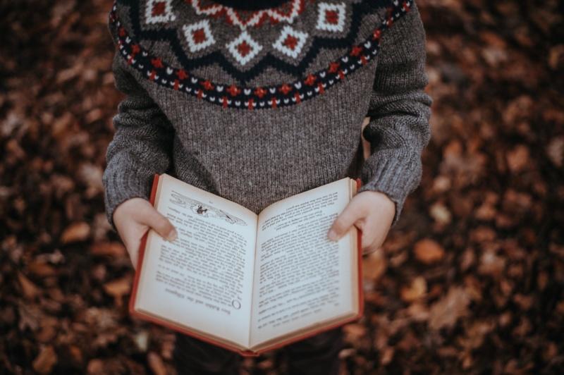 Person står i høstløvet med en åpen bok i hendene
