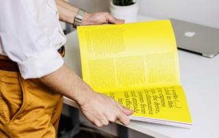 mann holder et magasin med knall gule sider